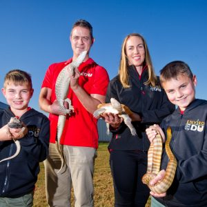 EnviroEdu. The Holmes family. Mali and a Bearded Dragon, Alex with a Sand Goanna, Sarah and a Broad-Shelled Turtle and Noah with a Woma Python.
